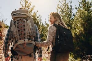 Couple with backpacks hiking on mountain